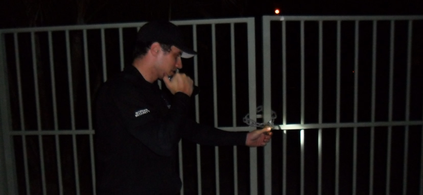 security guard checking lock on gate